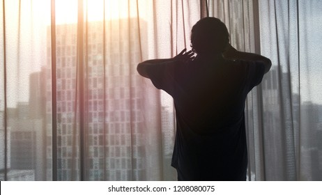 Young businessman opens curtains admire view from the window in business apartment during sunset