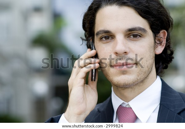 A young businessman outside holding a phone