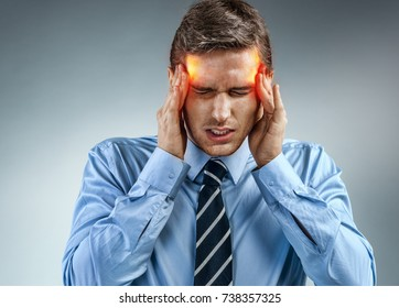 Young businessman with pain in his temples. Photo of man suffering from stress or a headache grimacing in pain. Medical concept