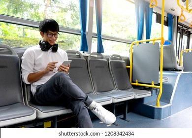 young businessman passenger use time in the bus it be lifestyle for transpotation in the city. he feel happy when use smart phone chat or read message.