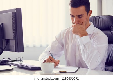 Young businessman with a pen in the office, toned