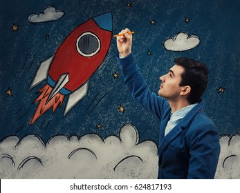 Young businessman with a pencil in his hand drawing as a rocket ship take off in cosmos. Business launch and development, the growth up of the economy, new project investments.