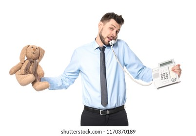 Young businessman with phone and bunny toy on white background