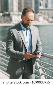 Young businessman with a phone in his hands, standing in a big city among high-rise buildings
