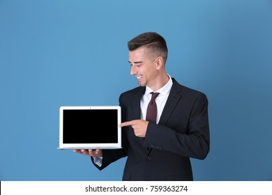 Young businessman pointing at laptop screen against color background
