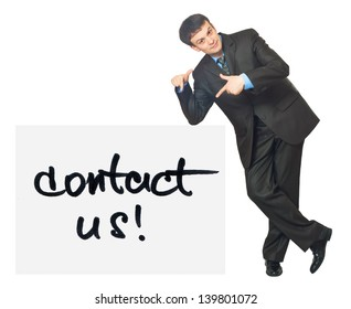 Young businessman points on a card Contact Us on a white background