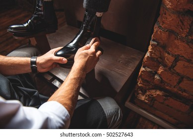 young businessman polishing footwear of the man