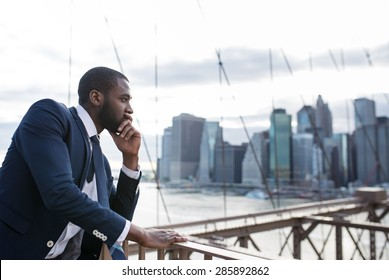 Young businessman portrait on Brooklyn Bridge. New York City.