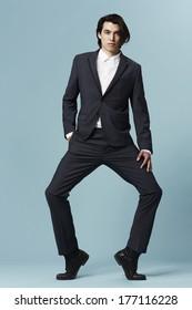 Young businessman posing on tip toe, studio shot