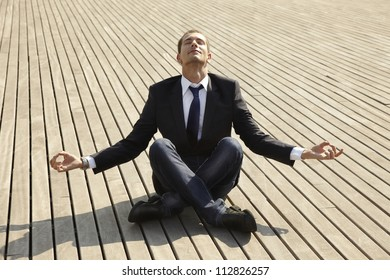 Young businessman in the position of the lotus. Man sitting at floor in a relaxation position