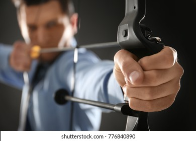 Young businessman practicing archery on dark background