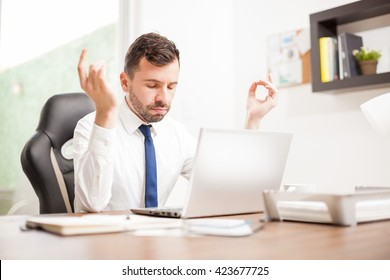 Young businessman practicing some breathing exercises at the office to manage stress and calm down