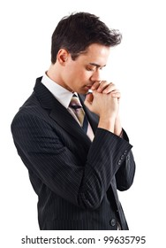 Young businessman praying. Isolated against white background.