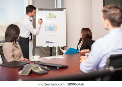 Young businessman presenting some results in a flipboard to a group of people in a meeting room