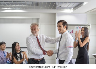 Young businessman promoted. Boss shaking hands with employee celebration for new position.