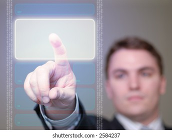 Young businessman pushing a brightly glowing area on a translucent, hi-tech screen. Shallow DOF.