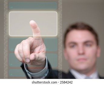 Young businessman pushing a button area on a translucent, hi-tech screen. Shallow depth of field.