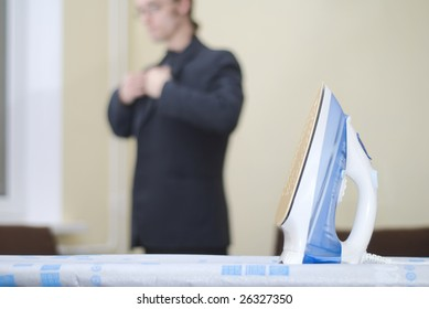 Young businessman putting on his jacket already pressed with iron