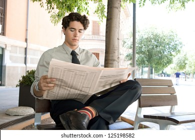 Young businessman reading a financial newspaper while sitting on a bench in the city, wearing quirky and colorful stripy socks.
