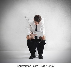 Young businessman reading a magazine on a toilet