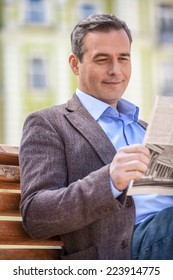 Young businessman reading newspaper while sitting on bench at park. gentleman sitting on wooden bench and reading newspaper in park