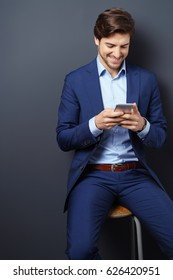 Young businessman reading a text message on his smartphone with a smile as he sits on a stool against a dark grey background with copy space
