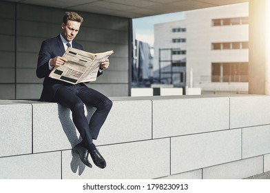 Young businessman reading through the financial section of a newspaper while sitting outside on the brick ledge of an office building