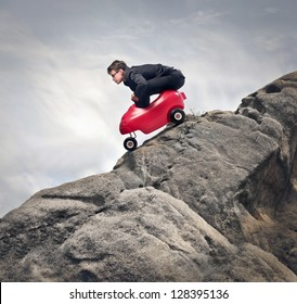 young businessman with red car descends from rocks