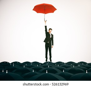 Young businessman with red umbrella flying above black umbrellas on light background. Leadership concept. 3D Rendering
