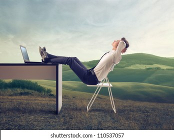 Young businessman relaxing at his desk in the middle of a green meadow