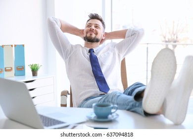 Young businessman relaxing at workplace with his feet on desk