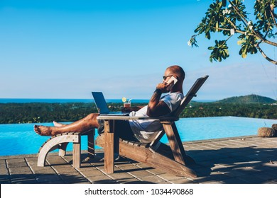 Young businessman resting on sunbed enjoying summertime in resort spa near swimming pool while working remotely at laptop computer connected to wireless internet and talking on smartphone with partner