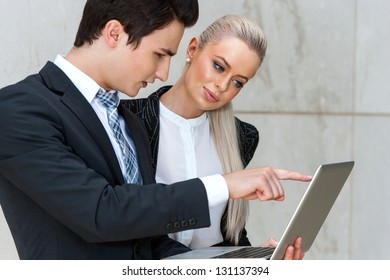 Young businessman reviewing work on laptop with attractive female colleague.