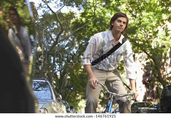 Young businessman riding bike on city street