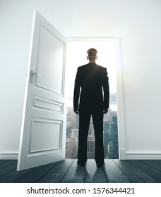 Young businessman in room with open door to city. Motivation and startup concept.