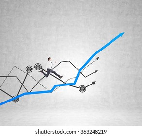 Young businessman running up a blue painted graph on a concrete wall. Other graphs at the background. Concept of growth.