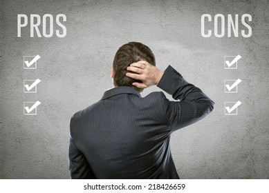 Young businessman selecting all pros and cons in front of grey wall. Portrait of financial manager comparing advantages and risks of investment deal.