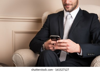 Young businessman sending message with mobile phone sit on armchair.