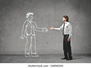 young businessman shaking hands with a man drawn on the wall