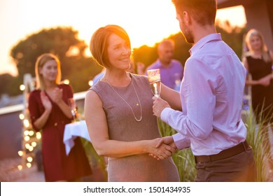Young businessman shaking hands with mature businesswoman during rooftop party