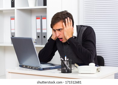 Young businessman is shocked by something he sees on his laptop monitor,Shocked businessman