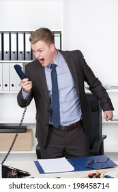 Young businessman is shouting into the phone while standing at the desk in the office. A shelf is in the background. The man is looking to the phone.