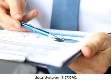The young businessman showing graphs by pen