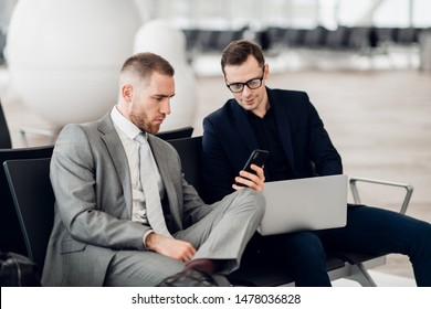 Young businessman showing a text message on his mobile phone to a male colleague at airport