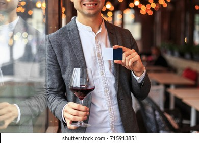 Young businessman shows business card in restourant with glass of red wine smiling
