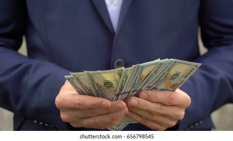 Young businessman shows his money close up