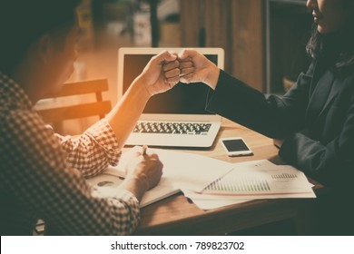 Young businessman is signing agreements with Asian business woman. They both use each other a fist bump. As a sign of cooperation with the balance of trade and investment.
