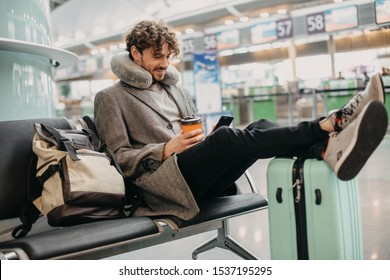 Young businessman sit alone and wait for flight. Hold phone in hands and cup of coffee. Flight pillow around neck. Expert or executive manager travel abroad. Waiting room