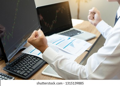 young businessman sit and look to the computer watch stock market. He excited when the stock market set index was the good point .