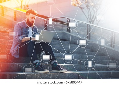 Young businessman sits outdoor on steps, using laptop and looks on his screen.Blockchain technology.Virtual icons.Hipster bearded man is working online,checking email.Student learning online.Lifestyle